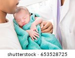doctor gently putting sleeping... | Shutterstock . vector #653528725