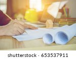Small photo of filled with building plans and background of Town planning,architect-man working with laptop and blueprints, architects sitting from behind working on architectural plan by calculator