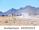 Small photo of A t-junction street sign near the town of solitaire in Namibia Southern Africa with a vehicle passing by on a gravel road in the dust against mountains