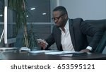 Small photo of Afro-american businessman reading emails on his smartphone and texting answers