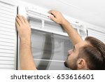 man installing window blinds at ...   Shutterstock . vector #653616601