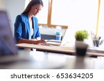 woman sitting on the desk with... | Shutterstock . vector #653634205