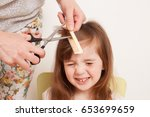 woman cuts the baby hair. the...
