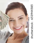 Small photo of Young beautiful casual woman holding large sum of money.