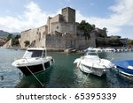 Collioure, harbour with several boats and at the background the castle - stock photo