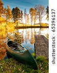 Stock photo a boat at the shore of a lake it is autumn the trees have red and yellow leaves 65396137