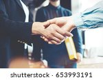 young business people shaking... | Shutterstock . vector #653993191