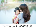 mom is holding in her arms her... | Shutterstock . vector #654032101