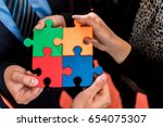business people solving jigsaw... | Shutterstock . vector #654075307