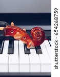 Small photo of violin headstock on piano keys, music background