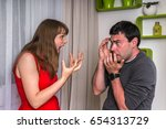 Small photo of Unhappy couple having argument at home - family quarrel concept