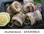 Stock photo herring fillet rolls served with green and red onion lemon and spices closeup selective focus 654345814