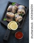 Stock photo herring fillet rolls with onion spices and lemon on a wooden serving board studio shot 654346054