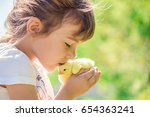 the child holds a chicken in... | Shutterstock . vector #654363241