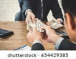 businessman giving money ... | Shutterstock . vector #654429385