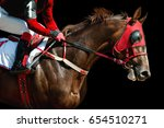 Stock photo jokey on a thoroughbred horse in red mask runs isolated on black background 654510271