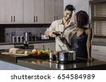 young mixed race couple cooking ... | Shutterstock . vector #654584989