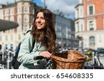 Small photo of Young happy woman on bicycle looking side and smiling in the city of Copenhagen, Denmark. Activity, healthy lifestyle and environmentally friendly transport