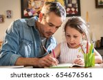 Small photo of A father helps his little daughter to do her homework for the school.