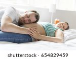 parents in bed expecting a... | Shutterstock . vector #654829459