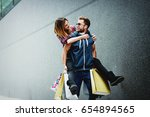 happy couple with shopping bags ... | Shutterstock . vector #654894565