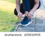 runner woman tying running... | Shutterstock . vector #655010935