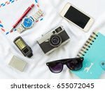 Small photo of Flat Lay photo with prop are Air letter, watch, pen, Flash, Camera, Glasses, Charger, Blue Notebook and smartphone on white fabric background.