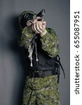 Small photo of The soldier in camouflage suit, body armor, in a gas mask with a hood on his head. To aim, shoot from a pistol. Man, stalker. Studio photo on a gray background