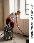 Small photo of Girl vacuum cleaning floor in abounded studio