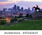 Small photo of View of Kansas City, Missouri skyline at dawn during golden light from the Kansas City Scout Memorial with all registered trademarks removed.