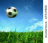soccer ball over green field - stock photo