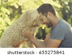 Stock photo man with his dog hugging and playing outdoor in the park young owner having fun with his pet in 655275841