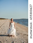 bride walking along sea coast... | Shutterstock . vector #655303627