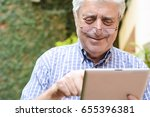 portrait of an old man using... | Shutterstock . vector #655396381