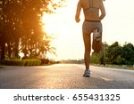 sporty woman running on road at ... | Shutterstock . vector #655431325