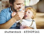young father at home feeding... | Shutterstock . vector #655439161