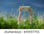 a woman lies on a grass and... | Shutterstock . vector #655557751