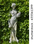 Small photo of A white sculpture surrounded by leafs in a natural framing. Classical Greek ornament with a woman and a pitcher.