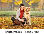 Stock photo a beautiful woman and his dog labrador retriever posing outside 65557780