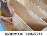mature man measuring wooden... | Shutterstock . vector #655601155