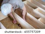 mature man measuring wooden... | Shutterstock . vector #655757209