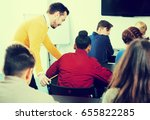 Small photo of happy american male teacher clearing up complicated issue to pupil during exam in class