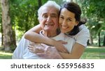Small photo of Granddaughter, nurse, caring for the elderly, girl (woman) hugging grandfather, smiling, happy, walking in the park. Concept: boarding house, sanatorium, a house for the elderly, help for the elderly.