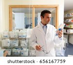 pharmacist looking at packet | Shutterstock . vector #656167759