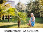 Small photo of Beautiful happy young slim girl sat around a small palm tree. In the blue dress, shawl pareo. Turkey. Palms. recreation. Vacation. Sunlight. close up.