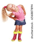 Small photo of An impish little blond girl in a blouse, a skirt and rubber boots isolated on white background.