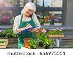 woman working in florist shop  | Shutterstock . vector #656975551