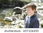 Young boy, looking out over the water from the riverside - stock photo