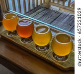 Small photo of Beer flight sampler on wooden paddle in front of a window