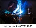 young industrial worker welding ... | Shutterstock . vector #657224059